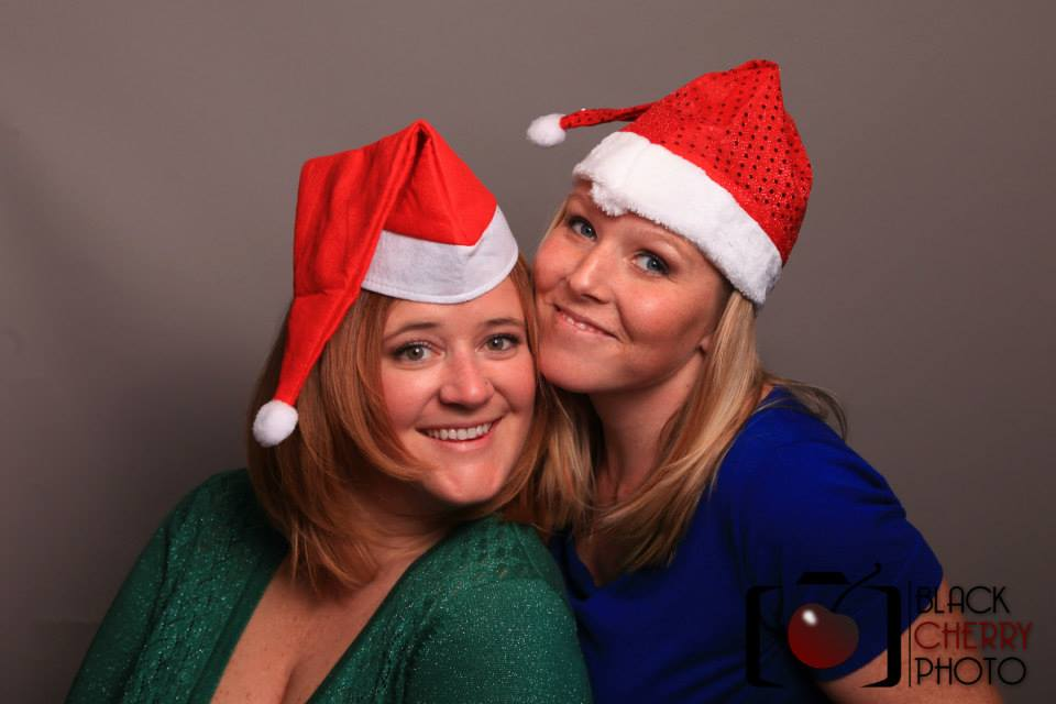 Photo Booth Rental Denver, Holiday Party photo booth rental Denver, 2 girls in Santa hats in a photo booth, photo booth for corporate holiday parties, Santa hats, photo booth Denver, photo booth rental Denver, holiday party rental, Christmas party rental